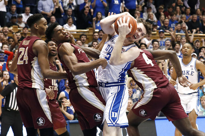 Duke forward Matthew Hurt, second from front right, grabs a rebound while Florida State guard Trent Forrest, guard Devin Vassell (24) and forward Patrick Williams (4) defend during the second half of an NCAA college basketball game in Durham, N.C., Monday, Feb. 10, 2020. (AP Photo/Gerry Broome)