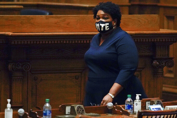 FILE - In this Dec. 14, 2020, file photo Democrat Stacey Abrams, walks on Senate floor before of members of Georgia's Electoral College cast their votes at the state Capitol in Atlanta. Abrams, Georgia's well-known voting rights advocate, is taking a carefully balanced approach in response to new laws many people have said are an attempt to suppress votes of people of color. When asked about the law changes, she is critical but measured. (AP Photo/John Bazemore, Pool, File)