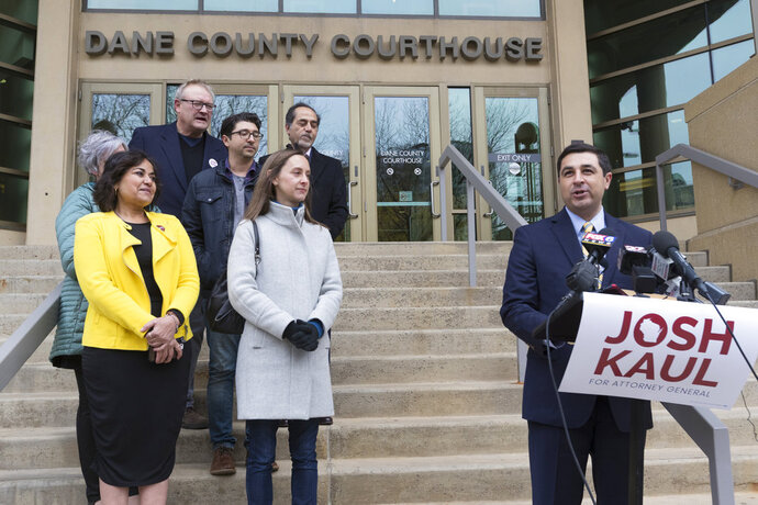 FILE - In this Wednesday, Nov. 7, 2018 file photo, Democratic candidate for state attorney general Josh Kaul, right, claims victory during a news conference at the Dane County Courthouse in Madison, Wis. Wisconsin's attorney general-elect, Kaul, campaigned on promises to pull the state out of a lawsuit challenging the Affordable Care Act and to get tougher on polluters. Republicans pushing to hang on to power in Wisconsin and Michigan are trying to hamstring Democrats who are about to take over as attorneys general. (Mark Hoffman/Milwaukee Journal-Sentinel via AP, File)