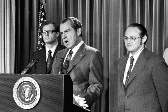 """FILE - In this June 17, 1971, file photo, President Richard Nixon explains aspects of the special message sent to the Congress, asking for an extra $155 million for a new program to combat the use of drugs. He labeled drug abuse """"a national emergency"""" and said the money would be used to """"tighten the noose around the necks of drug peddlers and thereby loosen the noose around the necks of drug users."""" At left is Egil Krogh, deputy director of the Domestic Council. At right is Dr. Jerome Jaffe, who was recruited by Nixon to lead a new drug strategy. (AP Photo/Harvey Georges, File)"""