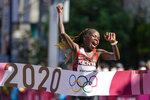 Peres Jepchirchir, of Kenya, celebrates as she crosses the finish line to win the women's marathon at the 2020 Summer Olympics, Saturday, Aug. 7, 2021, in Sapporo, Japan. (AP Photo/Eugene Hoshiko)