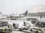 Snow falls on the United Terminal at O'Hare Airport in Chicago Monday morning, Nov. 11, 2019. (Daryl Van Schouwen/Chicago Sun-Times via AP)