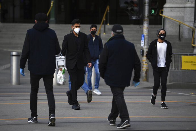 People wearing face masks to help protect against the spread of the new coronavirus walk outside Flinders Street Station in Melbourne, Australia, Thursday, July 23, 2020. There were few bare faces among rush-hour commuters in Australia's second-largest city on Thursday morning as Melbourne residents were largely complying with a new law making face coverings compulsory. (James Ross/AAP Image via AP)