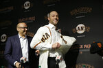 San Francisco Giants manager Gabe Kapler tries on his new jersey after being introduced by president of baseball operations Farhan Zaidi, left, during a news conference at Oracle Park Wednesday, Nov. 13, 2019, in San Francisco. Kapler has been hired as manager of the San Francisco Giants, a month after being fired from the same job by the Philadelphia Phillies. Kapler replaces Bruce Bochy, who retired at the end of the season following 13 years and three championships with San Francisco. (AP Photo/Eric Risberg)