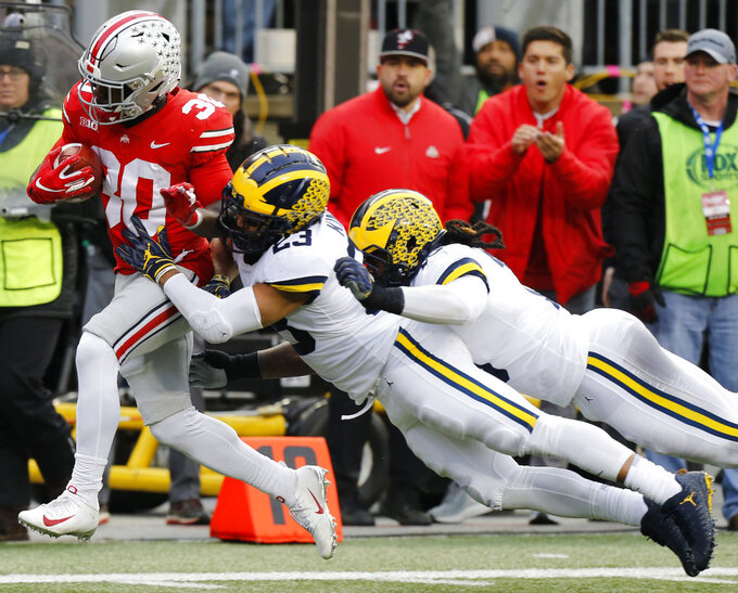 Ohio State running back Demario McCall, left, is tackled by Michigan defenders Tyree Kinnel, center, and Devin Bush during the first half of an NCAA college football game Saturday, Nov. 24, 2018, in Columbus, Ohio. (AP Photo/Jay LaPrete)