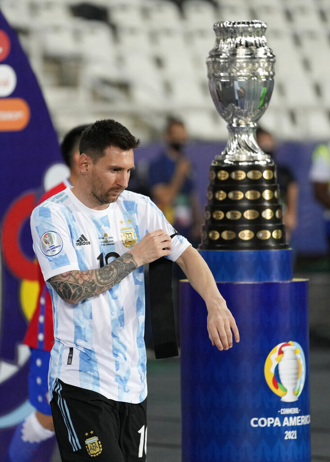 Argentina's Lionel Messi walks past the Copa America trophy as he enters the field for a soccer match against Chile at the Nilton Santos stadium in Rio de Janeiro, Brazil, Monday, June 14, 2021. (AP Photo/Ricardo Mazalan)