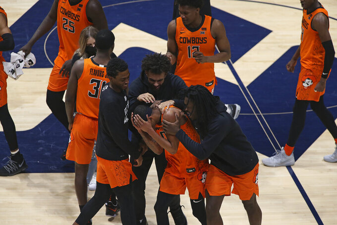 Oklahoma State guard Avery Anderson III, center, celebrates after defeating West Virginia in an NCAA college basketball game Saturday, March 6, 2021, in Morgantown, W.Va. (AP Photo/Kathleen Batten)
