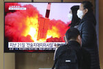 People pass by a TV screen showing a file image of North Korea's missile launch during a news program at the Seoul Railway Station in Seoul, South Korea, Sunday, March 29, 2020. North Korea on Sunday fired two suspected ballistic missiles into the sea, South Korea said, calling it