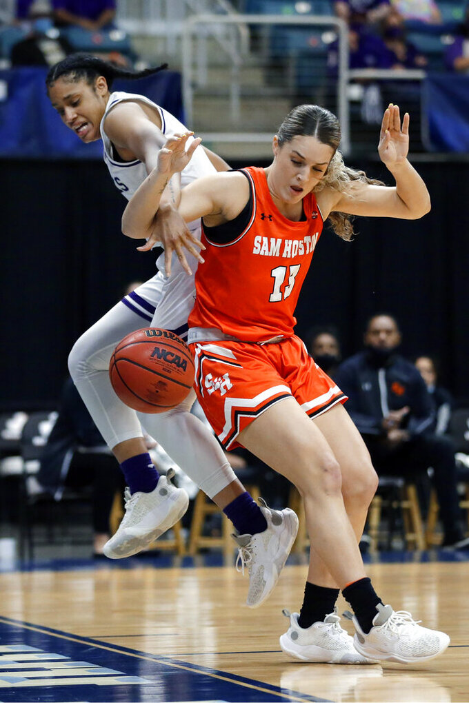 Stephen F. Austin guard Alyssa Mayfield, left, and Sam Houston State forward Kaylee Jefferson, right, tangle as they chase a loose ball during the first half of an NCAA college basketball game for the Southland Conference women's tournament championship Sunday, March 14, 2021, in Katy, Texas. (AP Photo/Michael Wyke)
