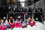 Supporters of former President Evo Morales sit in front of riot police in La Paz, Bolivia, Monday, Nov. 18, 2019. Morales's backers have taken to the streets since he resigned on Nov. 10 under pressure from the military after weeks of protests against him over a disputed election that he claimed to have won. (AP Photo/Natacha Pisarenko)