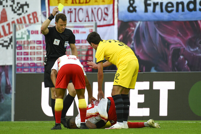 Dortmund's Giovanni Reyna, right, receives a yell card during the German Bundesliga soccer match between RB Leipzig and Borussia Dortmund in Leipzig, Germany, Saturday, June 20, 2020. (AP Photo/Jens Meyer, Pool)