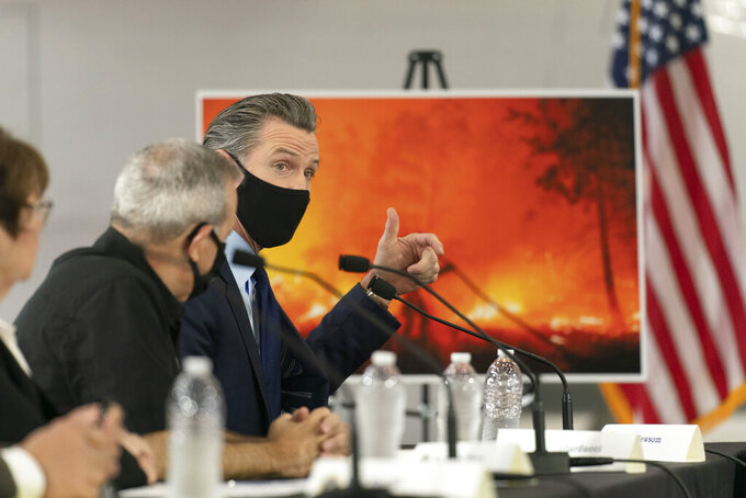 FILE - In this Sept. 14, 2020, file photo, California Gov. Gavin Newsom speaks about wildfires during a briefing with then President Donald Trump at Sacramento McClellan Airport in McClellan Park, Calif. California's governor is proposing spending $11 billion on programs to combat climate change amid a drought that followed a year of historic wildfires exacerbated by a warming planet. Gov. Newsom's revised $268 billion state budget proposal Friday, May 14, 2021, would vastly increase spending to clean up air pollution, shore up water supplies and prevent and contain wildfires. (AP Photo/Andrew Harnik, File)