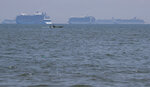 A boat passes by cruise ships carrying Filipino and foreign seafarers anchored at Manila's bay, Philippines, Thursday, May 7, 2020, as they wait clearance from the Bureau of Quarantine to dock at the port. Tens of thousands of workers have returned by plane and ships as the pandemic, lockdowns and economic downturns decimated jobs worldwide in a major blow to the Philippines, a leading source of global labor. (AP Photo/Aaron Favila)