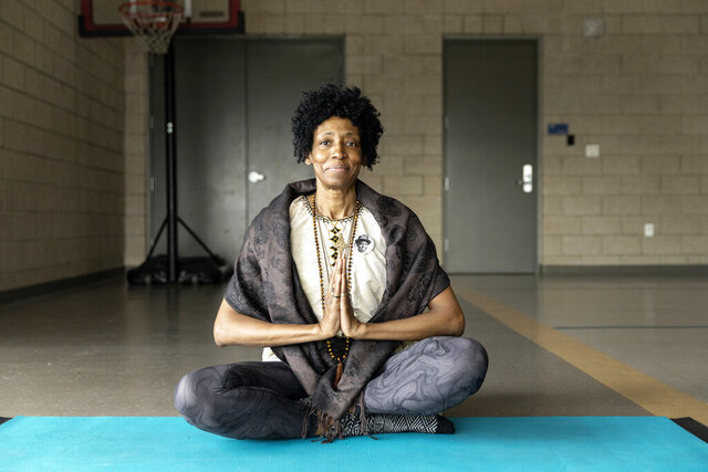 This Feb. 29, 2020 photo provided by Kaiser Health News shows Beverly Grant finding peace and balance through yoga and meditation in the midst of painful losses - her son's murder in 2018, and her mother's death earlier this year - at the Dahlia Campus of the Mental Health Center of Denver. A growing movement to diversify yoga seeks to help people of color who disproportionately share the experience of debilitating trauma and grief, including being most at risk of the coronavirus.   (Rebecca Stumpf for KHN via AP)