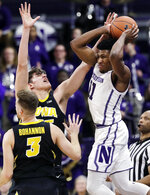 Northwestern guard Anthony Gaines, right, looks to pass against Iowa forward Luka Garza, center, and guard Jordan Bohannon during the first half of an NCAA college basketball game Wednesday, Jan. 9, 2019, in Evanston, Ill. (AP Photo/Nam Y. Huh)