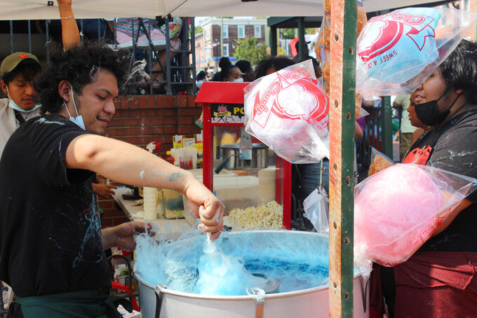 A vendor makes cotton candy at the Wilmington Hispanic Festival and Parade on Sunday, Sept. 12, 2021, in Wilmington, Del. People danced in the streets and watched from their doorsteps as passing parade floats serenaded Wilmington's majority-Hispanic Hilltop neighborhood on Sunday with the booming tunes of bachata and reggaetón. (José Ignacio Castañeda Perez/The News Journal via AP)