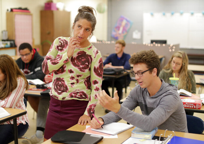 In a Wednesday, September 25, 2019 photo, English teacher Tmala Szyman, left, helps student Jacob Oppeneer understand a sentence structure concept during an English class at Oostburg High School, in Oostburg, Wis.  (Gary C. Klein/The Sheboygan Press via AP)