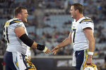 Los Angeles Chargers quarterback Philip Rivers, right, and center Scott Quessenberry, left, celebrate after scoring a touchdown against the Jacksonville Jaguars during the second half of an NFL football game, Sunday, Dec. 8, 2019, in Jacksonville, Fla. (AP Photo/Phelan M. Ebenhack)