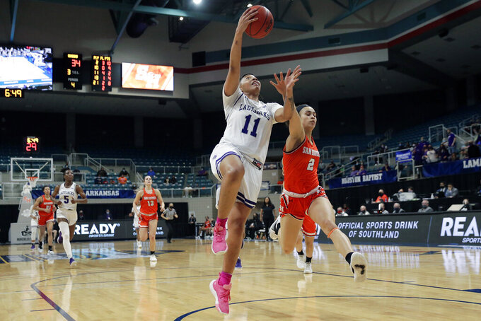 Stephen F. Austin forward Avery Brittingham (11) puts up a shot past Sam Houston State forward Amber Leggett (2) during the second half of an NCAA college basketball game for the Southland Conference women's tournament championship Sunday, March 14, 2021, in Katy, Texas. (AP Photo/Michael Wyke)