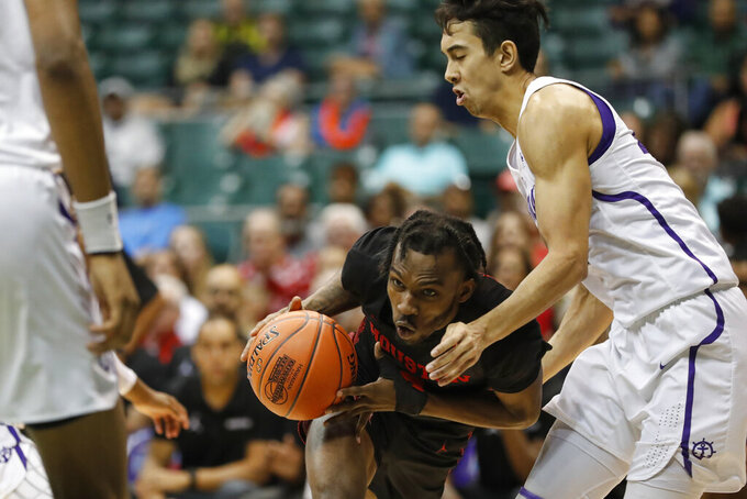 Houston guard Caleb Mills, center, pushes to get around Portland guard Takiula Fahrensohn, right, during the second half of an NCAA college basketball game Sunday, Dec. 22, 2019, in Honolulu. (AP Photo/Marco Garcia)