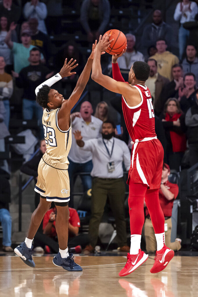 Arkansas guard Mason Jones (15) shoots the game-winning 3-pointer over Georgia Tech guard Asanti Price (23) in overtime of an NCAA college basketball game Monday, Nov. 25, 2019, in Atlanta. Arkansas won 62-61. (AP Photo/Danny Karnik)