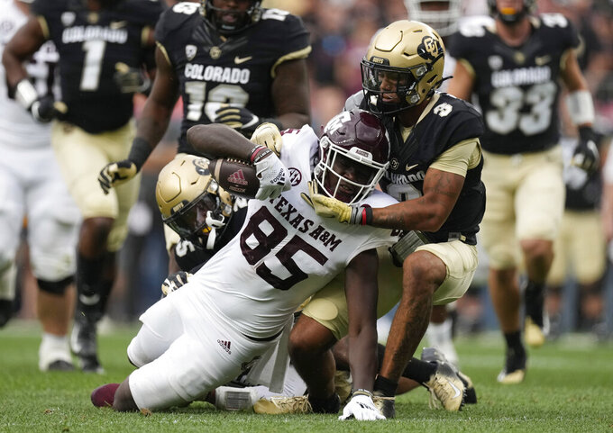 Texas A&M tight end Jalen Wydermyer, left, is tackled by Colorado cornerback Christian Gonzalez in the first half of an NCAA college football game Saturday, Sept. 11, 2021, in Denver. (AP Photo/David Zalubowski)