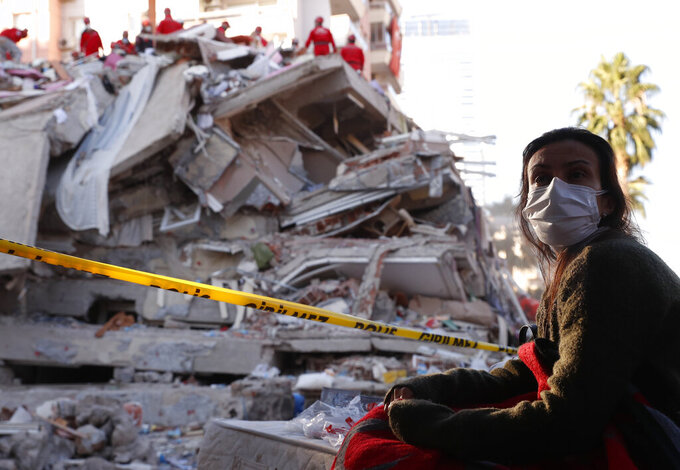 A local resident, staying outdoors for fear of aftershocks, watches as members of rescue services search for survivors in the debris of a collapsed building in Izmir, Turkey, Saturday, Oct. 31, 2020. Rescue teams on Saturday ploughed through concrete blocs and debris of eight collapsed buildings in Turkey's third largest city in search of survivors of a powerful earthquake that struck Turkey's Aegean coast and north of the Greek island of Samos, killing dozens Hundreds of others were injured. (AP Photo/Darko Bandic)