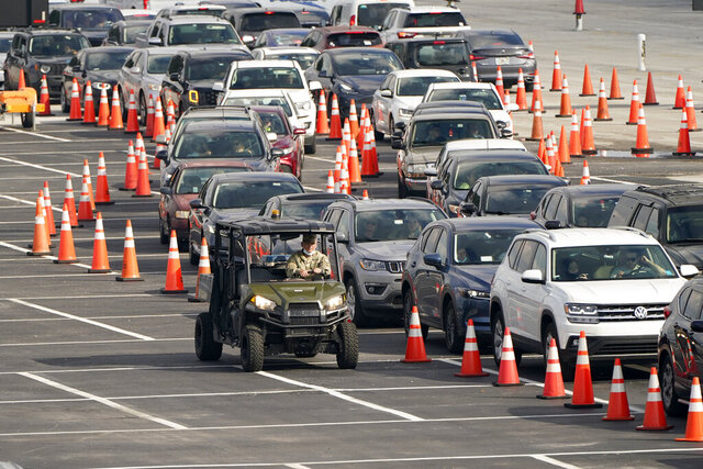 Vehicles wait in line at a COVID-19 testing site at Hard Rock Stadium, Monday, Nov. 23, 2020, in Miami. (AP Photo/Lynne Sladky)