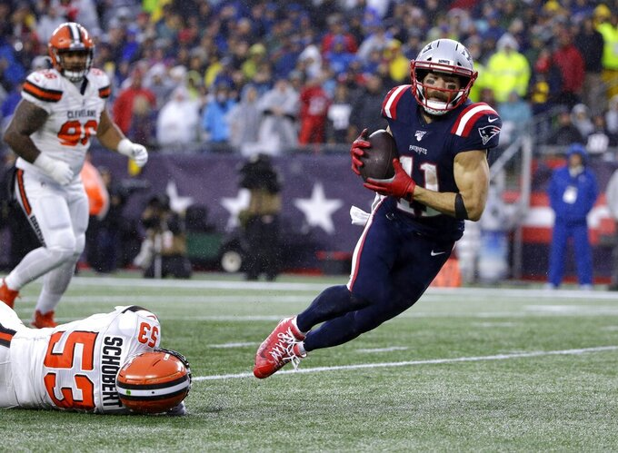 New England Patriots wide receiver Julian Edelman, right, runs from Cleveland Browns linebacker Joe Schobert, on the ground, for a touchdown after catching a pass in the first half of an NFL football game, Sunday, Oct. 27, 2019, in Foxborough, Mass. (AP Photo/Steven Senne)
