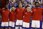 Kansas seniors Isaiah Moss, left, and Udoka Azubuike, right, stand with teammates Devon Dotson, second from left, Tristan Enaruna, middle, and Elijah Elliott, second from right, before an NCAA college basketball game against TCU in Lawrence, Kan., Wednesday, March 4, 2020. (AP Photo/Orlin Wagner)