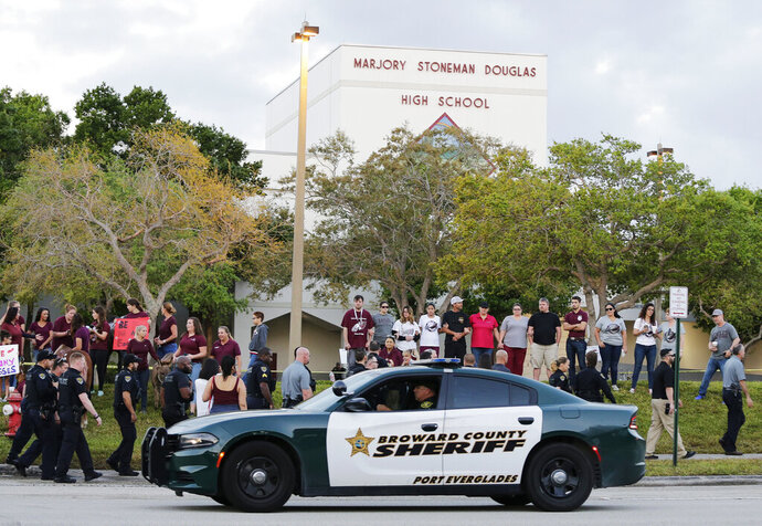 FILE - In this Feb. 28, 2018 file photo, a police car drives near Marjory Stoneman Douglas High School in Parkland, Fla., as students return to class for the first time since a former student opened fire there with an assault weapon. Republican Florida Gov. Ron DeSantis has signed a bill that will allow more classroom teachers to carry guns in school, a response to last year's mass shooting at a Parkland high school. (AP Photo/Terry Renna, File)