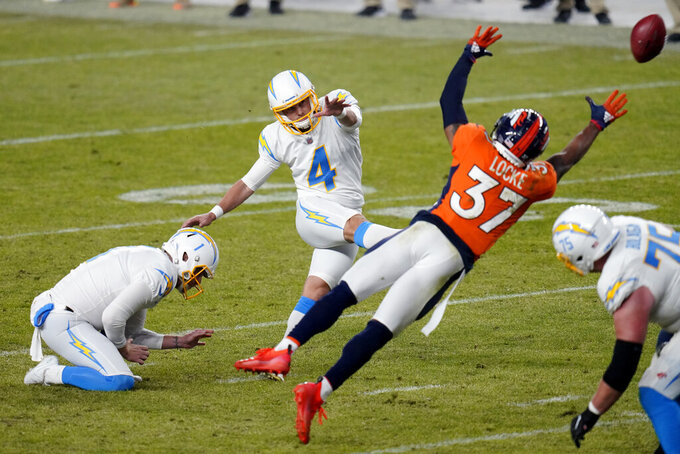 Los Angeles Chargers kicker Mike Badgley (4) kicks a field goal while punter Ty Long (1) holds as Denver Broncos defensive back P.J. Locke (37) defends during the second half of an NFL football game, Sunday, Nov. 1, 2020, in Denver. (AP Photo/Jack Dempsey)