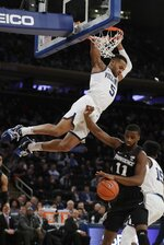 Villanova's Phil Booth (5) hangs from the rim over Providence's Alpha Diallo (11) after after dunking the ball during the first half of an NCAA college basketball game in the Big East conference tournament, Thursday, March 14, 2019, in New York. (AP Photo/Frank Franklin II)