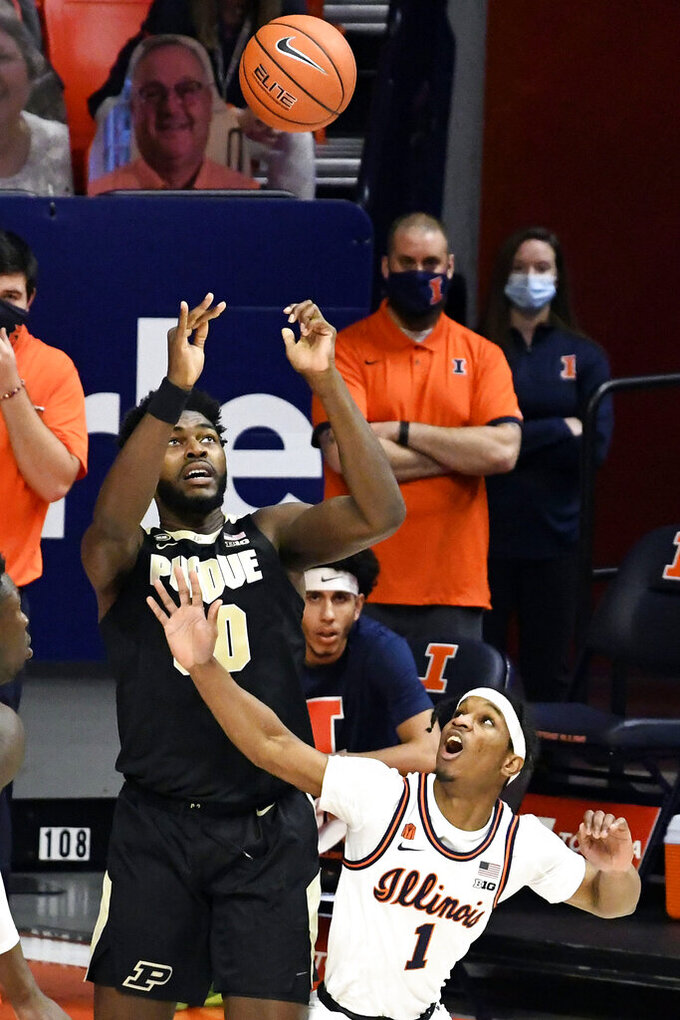 Purdue's forward Trevion Williams (50) tries to control the ball after it is tipped by Illinois guard Trent Frazier (1) in the first half of an NCAA college basketball game Saturday, Jan. 2, 2021, in Champaign, Ill. (AP Photo/Holly Hart)