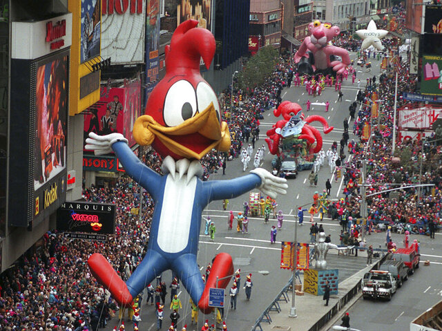 FILE - In  this Nov. 23, 1995 file photo Woody Woodpecker leads a line of other balloons and floats into New York's Times Square during the 69th annual Macy's Thanksgiving Day parade. A Macy's Thanksgiving parade reimagined for the coronavirus pandemic will feature floats, performers and giant balloons parading along a one-block stretch of 34th Street in front of the retailer's flagship Manhattan store, Macy's officials announced Monday, Sept. 14, 2020. (AP Photo/Paul Hurschmann, File)
