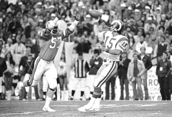 FILE - In this Sunday, Jan. 6, 1980, file photo, Tampa Bay Buccaneers' David Lewis, left, pressures Los Angeles Rams quarterback Vince Ferragamo during the NFC championship NFL football game in Tampa. Lewis, a key member of the Buccaneers' historic 1979 team that reached the NFC title game, has died. He was 65.  Lewis died Tuesday, July 14, 2020, in Tampa. The cause was not immediately known, but he had struggled with health issues in recent years. (AP Photo/File)