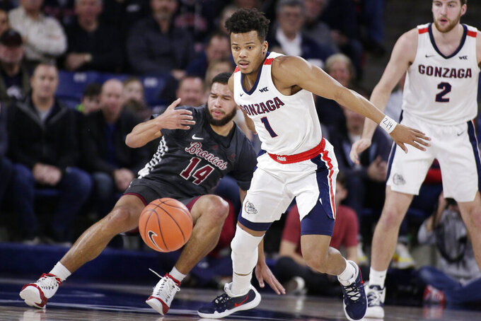 Gonzaga guard Admon Gilder (1) goes after the ball, after knocking it away from Santa Clara forward Keshawn Justice (14) during the first half of an NCAA college basketball game in Spokane, Wash., Thursday, Jan. 16, 2020. (AP Photo/Young Kwak)