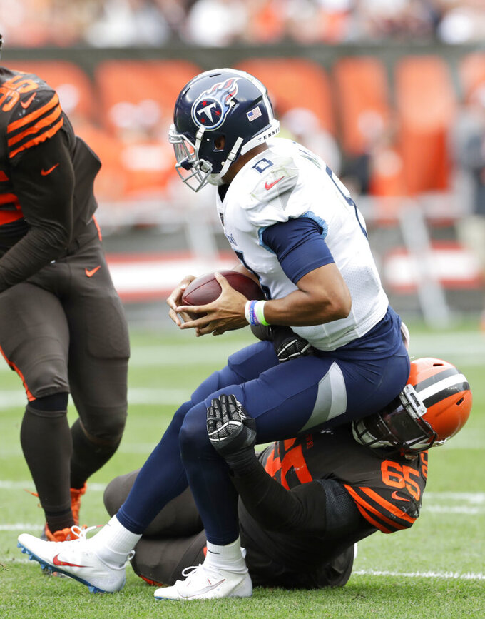 Cleveland Browns defensive tackle Larry Ogunjobi (65) sacks Tennessee Titans quarterback Marcus Mariota (8) during the second half in an NFL football game Sunday, Sept. 8, 2019, in Cleveland. (AP Photo/Ron Schwane)