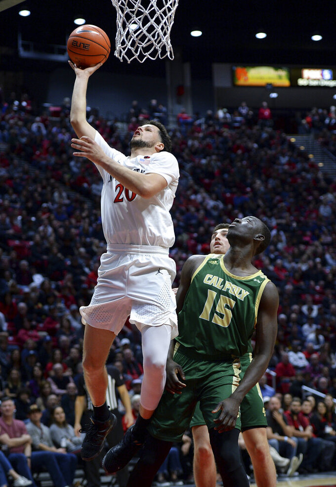 San Diego State guard Jordan Schakel (20) goes to the basket as Cal Poly forward Alimamy Koroma (15) watches during the first half of an NCAA college basketball game Saturday, Dec. 28, 2019, in San Diego. (AP Photo/Orlando Ramirez)