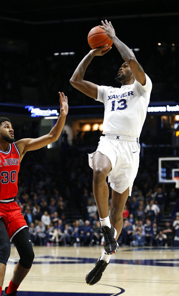Xavier forward Naji Marshall (13) shoots against St. John's guard LJ Figueroa (30) during the first half of an NCAA college basketball game, Sunday, Jan. 5, 2020, in Cincinnati. (AP Photo/Gary Landers)
