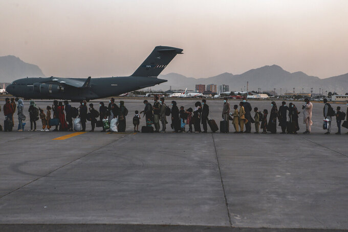 In this image provided by the U.S. Marine Corps,  evacuees wait to board a Boeing C-17 Globemaster III, at Hamid Karzai International Airport, Kabul, Afghanistan, Monday, Aug. 23, 2021. (Sgt. Isaiah Campbell/U.S. Marine Corps via AP)