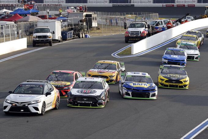 Cars come to a stop during a red flag late in the NASCAR Cup Series auto race at Charlotte Motor Speedway in Concord, N.C., Sunday, Sept. 29, 2019. (AP Photo/Gerry Broome)