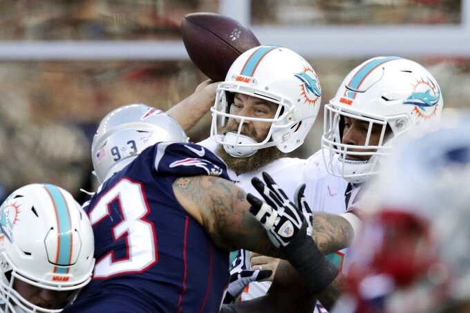 Miami Dolphins quarterback Ryan Fitzpatrick passes under pressure from New England Patriots defensive tackle Lawrence Guy in the first half of an NFL football game, Sunday, Dec. 29, 2019, in Foxborough, Mass. (AP Photo/Charles Krupa)