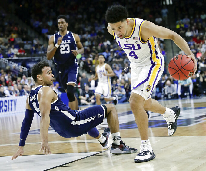 Yale 's Azar Swain, left, falls backward as LSU's Skylar Mays (4) drives past him to the basket during the first half of a first round men's college basketball game in the NCAA Tournament in Jacksonville, Fla., Thursday, March 21, 2019. (AP Photo/John Raoux)