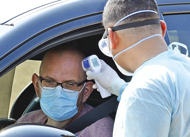 U. S. Army, Arizona National Guard Pvt. Ronald Aguilar, right, takes the temperature of a man at a drive-thru COVID-19 saliva test on the main campus at Arizona Western College, Saturday, Oct. 17, 2020, in Yuma, Ariz. The testing, organized by the Yuma County Public Health Services District, lasted from 11 a.m. to 3 p.m., and saw 671 tests administered, according to Yuma County spokesperson Kevin Tunnell. The purpose of the testing, according to Yuma County, was to capitalize on the recent development of a saliva test for COVID-19 by Arizona State University's Biodesign Institute. (Randy Hoeft/The Yuma Sun via AP)