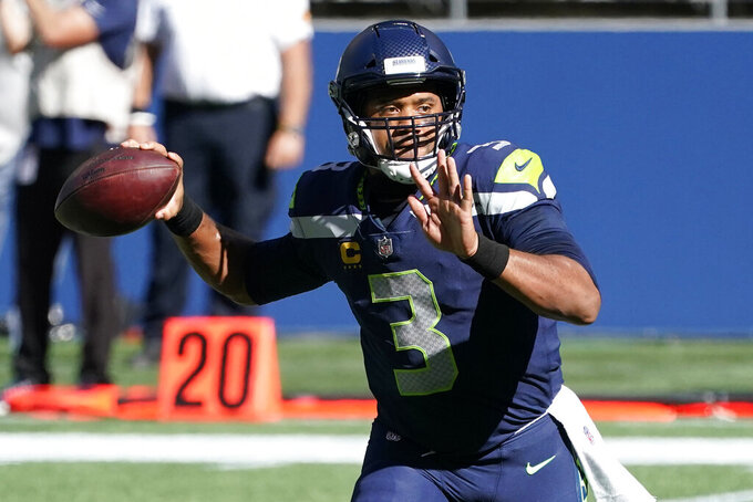 Seattle Seahawks quarterback Russell Wilson passes to wide receiver Tyler Lockett for a touchdown against the Dallas Cowboys during the first half of an NFL football game, Sunday, Sept. 27, 2020, in Seattle. (AP Photo/Elaine Thompson)