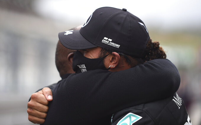 Mercedes driver Lewis Hamilton of Britain, right, is congratulated by his father Anthony Hamilton after his record breaking win at the Formula One Portuguese Grand Prix at the Algarve International Circuit in Portimao, Portugal, Sunday, Oct. 25, 2020. (Jorge Guerrero, Pool via AP)