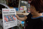 "FILE - In this June 12, 2018, file photo, a newspaper vendor holds up a front page photo of the meeting in Singapore between U.S. President Donald Trump and North Korean leader Kim Jong Un at a newsstand in Beijing, China. As soon as Kim steps off the airplane China provided him for the Singapore trip, Beijing will be mindful of maintaining its influence over a Pyongyang that may feel less isolated after Trump showered Kim with praises, called him a ""very talented man,"" and made security concessions in return for very little. (AP Photo/Ng Han Guan, File)"
