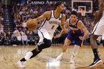 Brooklyn Nets guard Spencer Dinwiddie (8) drives around Phoenix Suns guard Devin Booker (1) during the second half of an NBA basketball game Sunday, Nov. 10, 2019, in Phoenix. (AP Photo/Matt York)