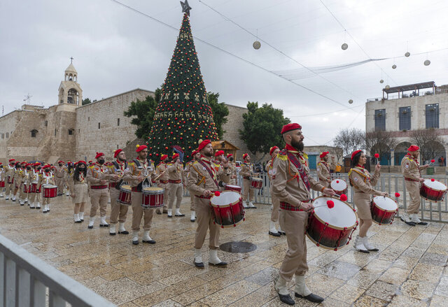 Palestinian scout bands parade through Manger Square at the Church of the Nativity, traditionally recognized by Christians to be the birthplace of Jesus Christ, ahead of the midnight Mass, in the West Bank city of Bethlehem, Thursday, Dec. 24, 2020. Few people were there to greet them as the coronavirus pandemic and a strict lockdown dampened Christmas Eve celebrations. (AP Photo/Nasser Nasser)